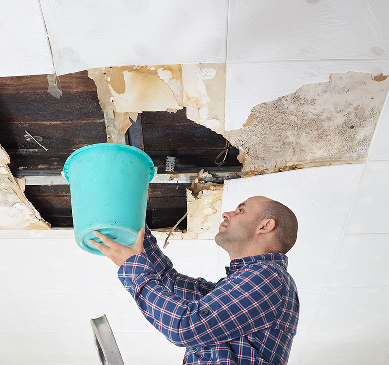Man Collecting Water from Huge Hole in Roof after Rain