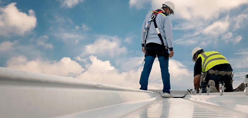Roofer Inspecting the Installation of Metal Roofing Work