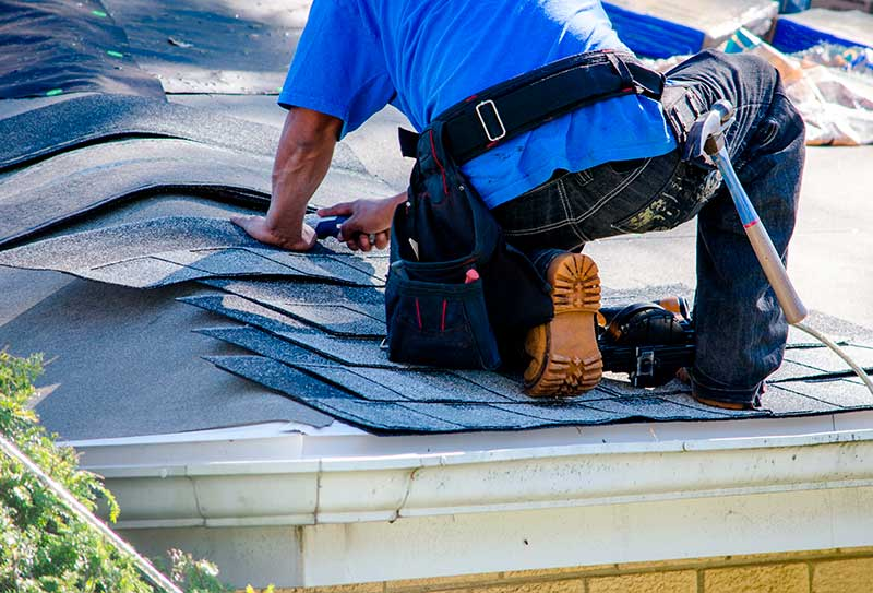 A Worker Replaces Shingles on the Roof of a Home