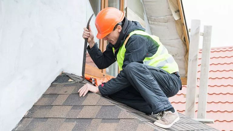 Roofer Dismantling Roof Shingles to Do Repairs