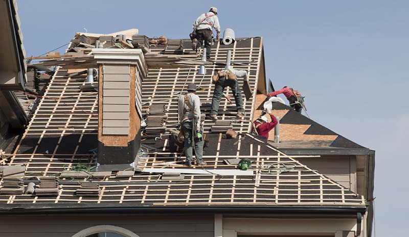 Crew of Roofers Working on Apartment Roof