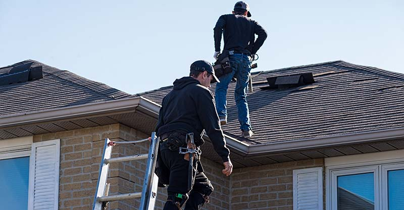 Roofing Workers Inspecting Damaged Roof